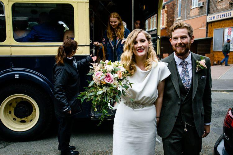 Bride in Vintage Wedding Dress and Groom in Tailored Suit  Getting off Wedding Bus