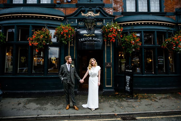 Bride with Satin Wedding Dress, Finger Waves and Red Lipstick, Holding Grooms Hand in Tailored Suit Outside Wedding Venue