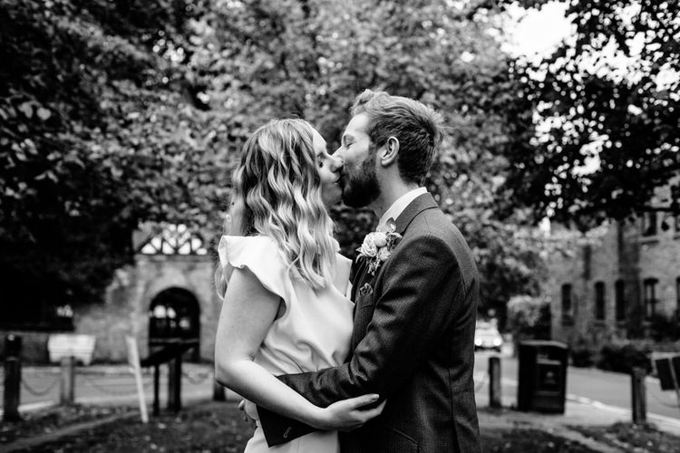 Vintage Bride with Satin Wedding Dress and  Finger Waves Kissing Groom in Tailored Wedding Suit