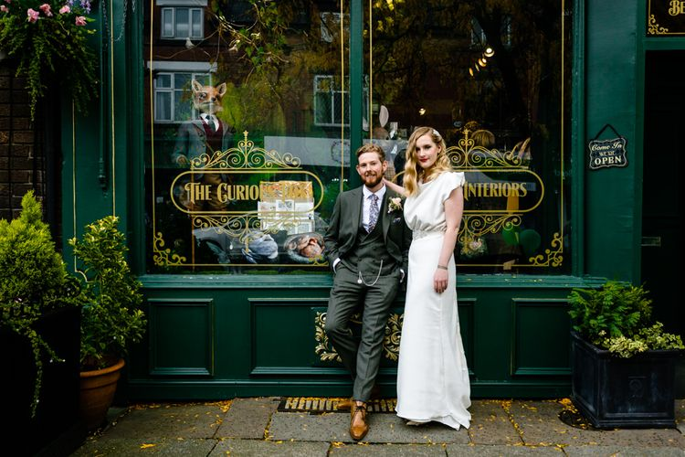 Vintage Bride Wearing a Satin Wedding Dress with Finger Waves and Red Lipstick, Standing with Groom in Tailored Suit Outside Wedding Venue