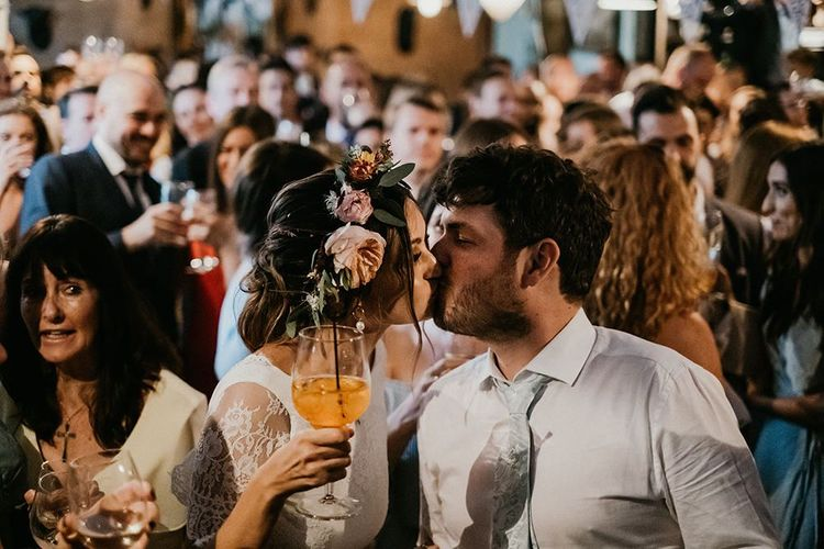 Bride and groom kiss amongst wedding guests at pub party