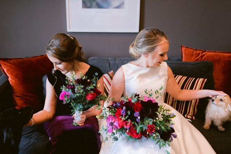 Bride with bridesmaid in plum dresses and family pets at wedding