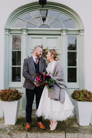 Bride wears tea-length dress and knitted grey cover-ip