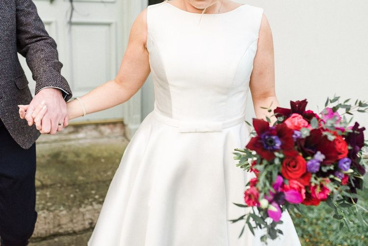 Tea-length wedding dress with jewel coloured bouquet