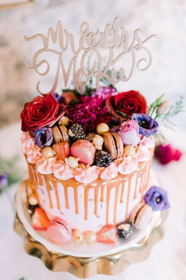 Amazing drip wedding cake with macaron cake topper and floral decor for Christmas wedding