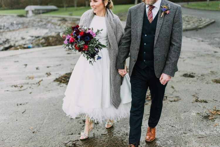 Tea-length wedding dress for Christmas wedding with red and purple bouquet