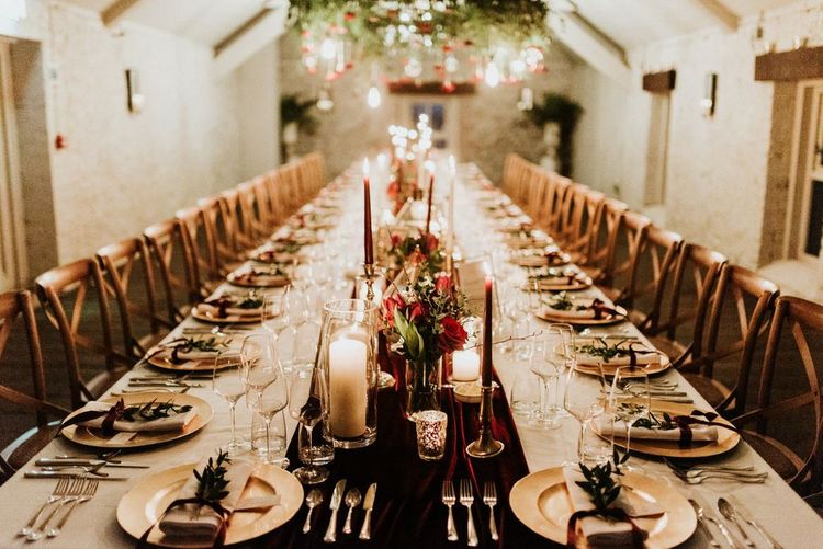 Cosy table decor with candles, gold candlesticks and flowers at Christmas wedding