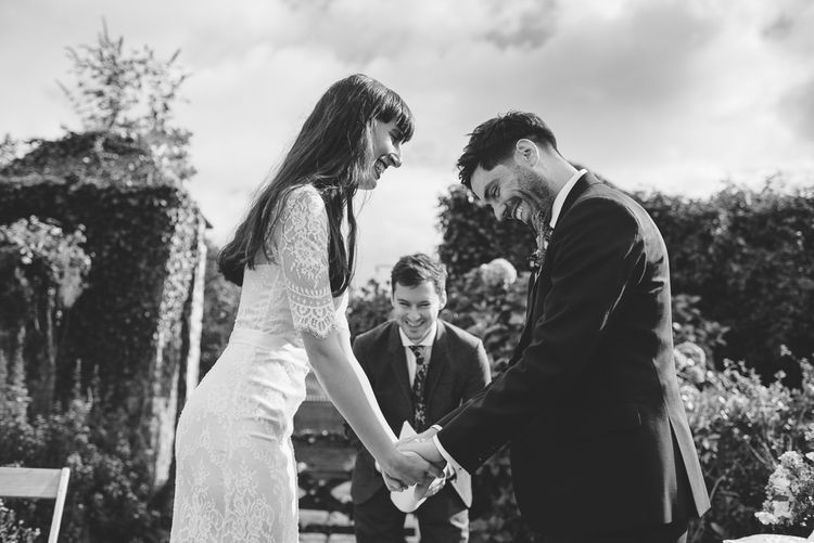 Bride and Groom Holding Hands and Laughing at their Persian Wedding