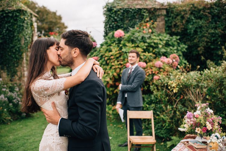Bride in Catherine Deane Wedding Dress and Groom in Paul Smith Suit Kissing at the Altar