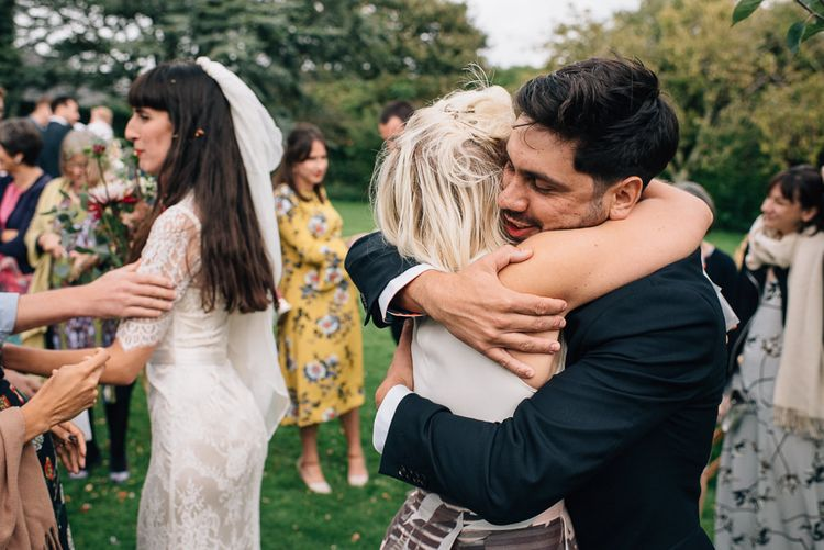 Bride and Groom Being Hugged by Wedding Guests after Just Getting Married