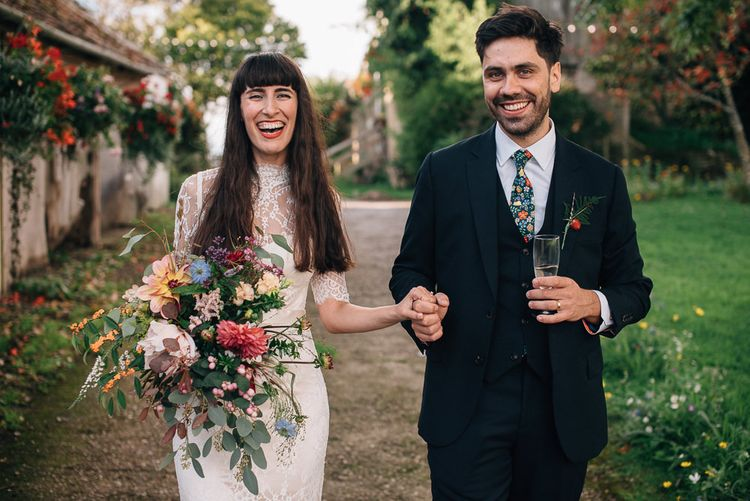 Bride in Catherine Deane Wedding Dress with Wild Flower Bouquet and Groom in Paul Smith Suit and Floral Liberty Print Tie