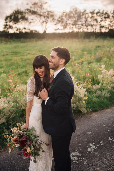 Bride in Catherine Deane Wedding Dress with Wild Flower Bouquet and Groom in Paul Smith Suit and Floral Liberty Print Tie Laughing Together