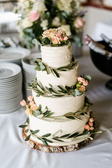 buttercream wedding cake decorated with olive leaves and pink flowers