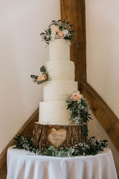 Tall buttercream rustic wedding cake on carved tree stump cake stand