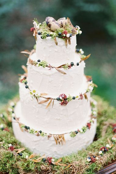 Rustic wedding cake resting on a bed of moss and topped with tiny eggs - rustic wedding cakes