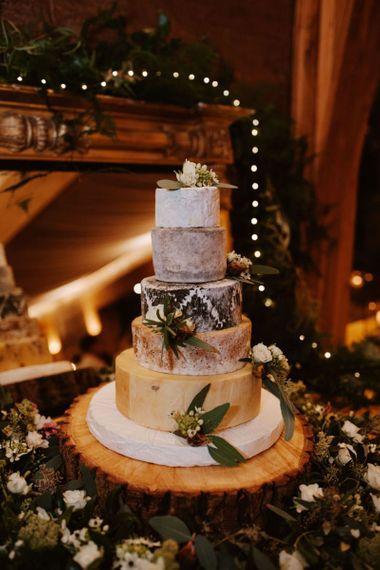 Cheese tower rustic wedding cake resting on tree slice - rustic wedding cakes