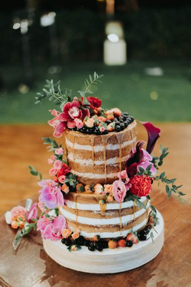 Naked drip wedding cake decorated with bright flowers