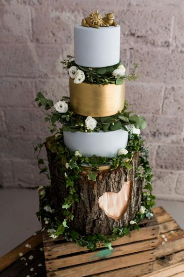 Blue and gold layered rustic wedding cake on Tree stump cake stand