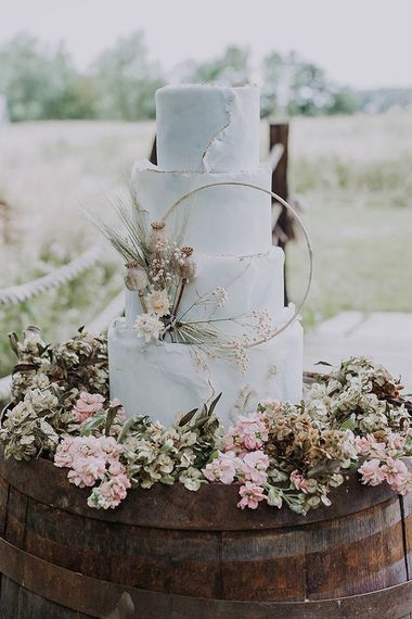 Pale blue iced rustic wedding cake on wooden barrel - rustic wedding cakes