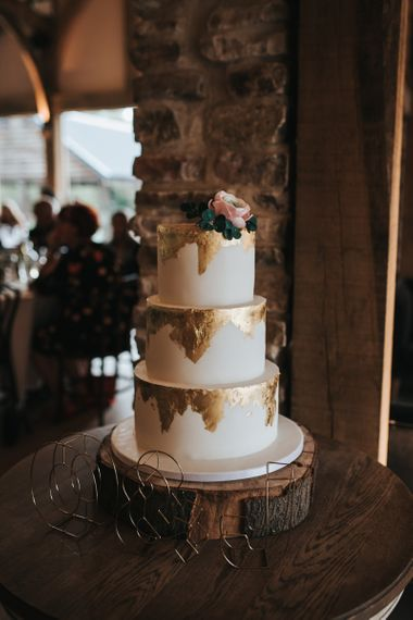 Iced wedding cake with gold leaf detail