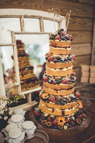 Tall naked wedding cake with berry decor - rustic wedding cakes
