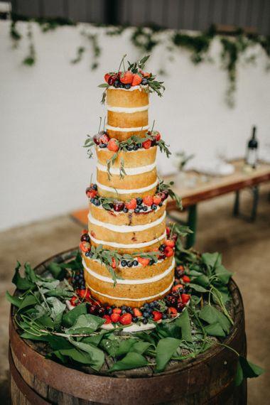 Tall naked wedding cake sitting on wooden barrel