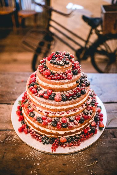 Naked sponge wedding cake decorated with berries - rustic wedding cakes
