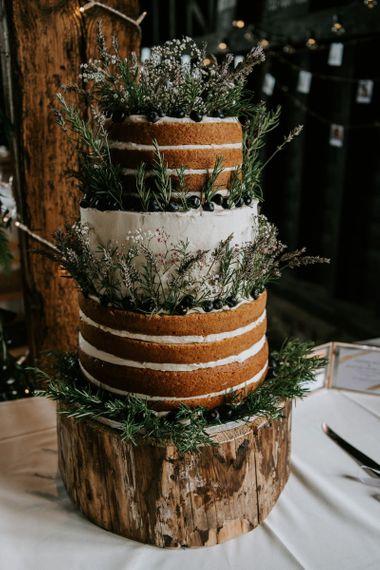 Rustic wedding cake with naked layers, foliage decor & tree stump cake stand