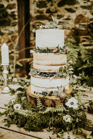 Semi naked rustic wedding cake decorated with succulents and figs