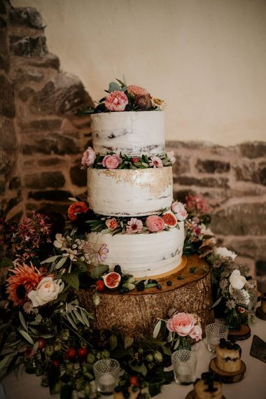 Semi naked rustic wedding cake decorated with pink flowers