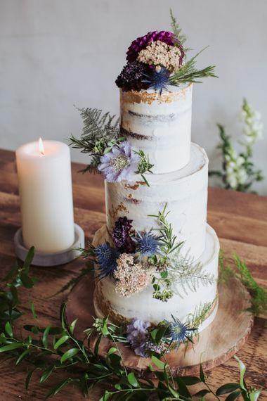 Semi naked wedding cake on wooden tree slice