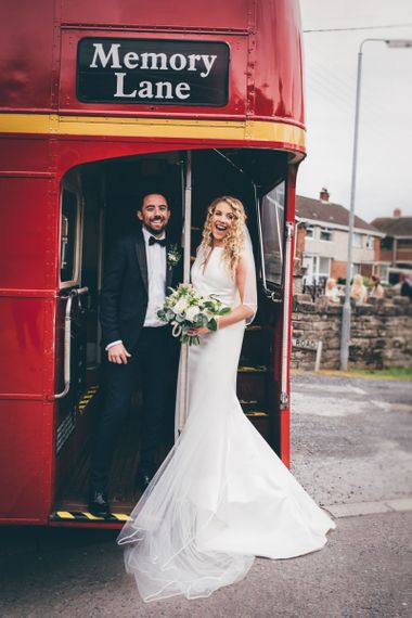 Bride in Satin Jesus Peiro Dress with V-Neck and Waist Bow with Beaded Belt | Floor Length Double Tier Veil with Blusher | Bridal Bouquet of White Flowers and Foliage | Groom in Black Tie Suit from Moss Bros. with Bow Tie | Vintage Red Routemaster Bus for Wedding Party | Nautical Wedding on SS Nomadic Boat in Belfast with Black Tie Dress Code | Sarah Gray Photography