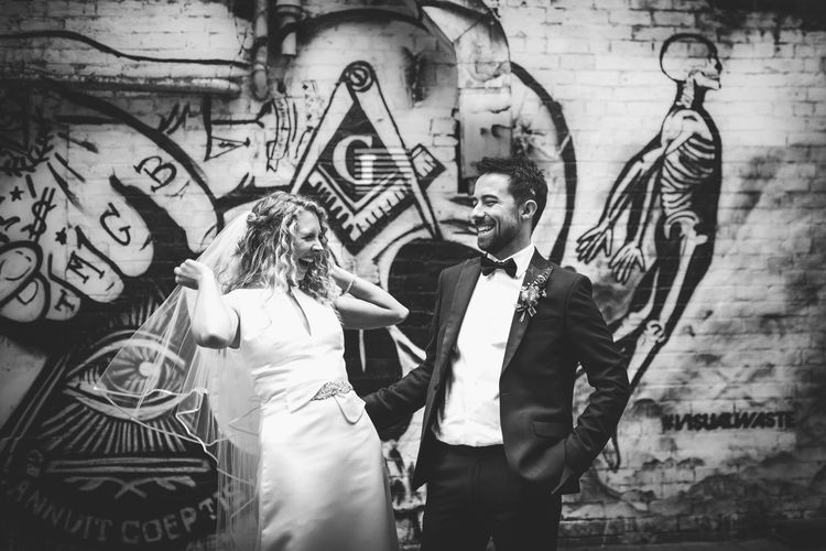 Bride in Satin Jesus Peiro Dress with V-Neck and Waist Bow with Beaded Belt | Floor Length Double Tier Veil with Blusher | Groom in Black Tie Suit from Moss Bros. with Bow Tie | Nautical Wedding on SS Nomadic Boat in Belfast with Black Tie Dress Code | Sarah Gray Photography