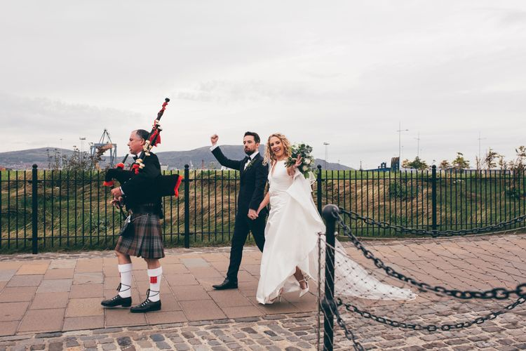 Bride in Satin Jesus Peiro Dress with V-Neck and Waist Bow with Beaded Belt | Floor Length Double Tier Veil with Blusher | Bridal Bouquet of White Flowers and Foliage | White Slingback Heels | Groom in Black Tie Suit from Moss Bros. with Bow Tie | Father of the Bride in Traditional Kilt Playing Bagpipes | Nautical Wedding on SS Nomadic Boat in Belfast with Black Tie Dress Code | Sarah Gray Photography