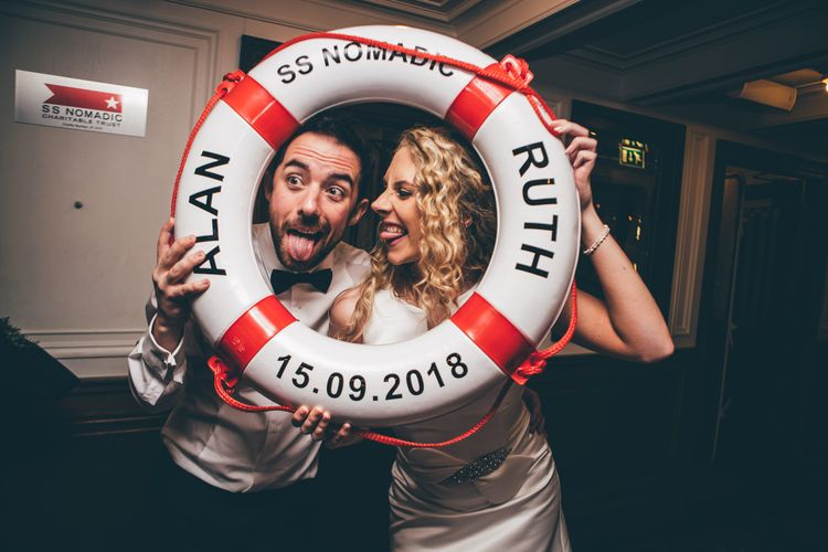 Bride in Satin Jesus Peiro Dress with V-Neck and Waist Bow with Beaded Belt | Groom in Black Tie Suit from Moss Bros. with Bow Tie | Wedding Reception on SS Nomadic, Belfast | Nautical Wedding on SS Nomadic Boat in Belfast with Black Tie Dress Code | Sarah Gray Photography