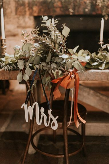Mrs chair back wedding decor with foliage and ribbon