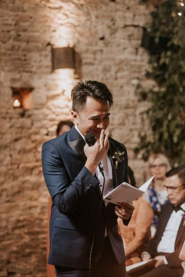 Emotional groom reading his vows during the wedding ceremony