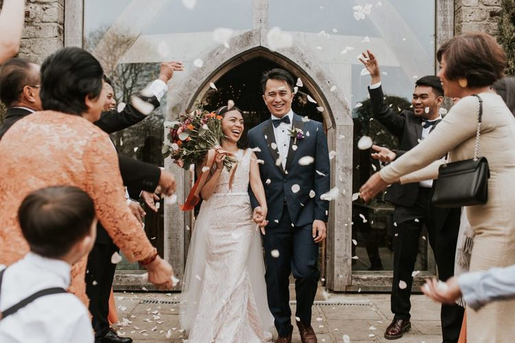 Bride and groom confetti exit at Cripps Barn