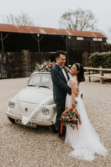 Bride and groom standing next to their Fiat 500 wedding car