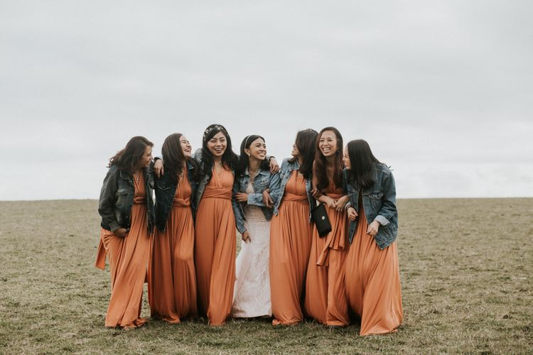 Bridal party portrait with bridesmaids in orange dresses and denim jackets