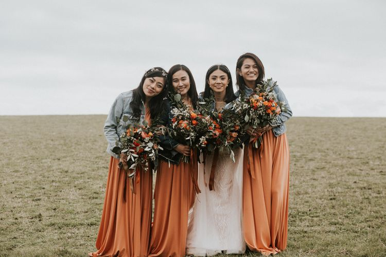 Bridesmaids in demin jackets, orange dresses and foliage bouquets