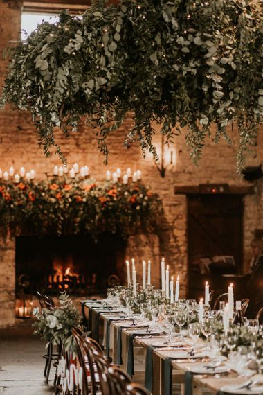 Intimate candle lit wedding reception at Cripps Barn with foliage chandelier