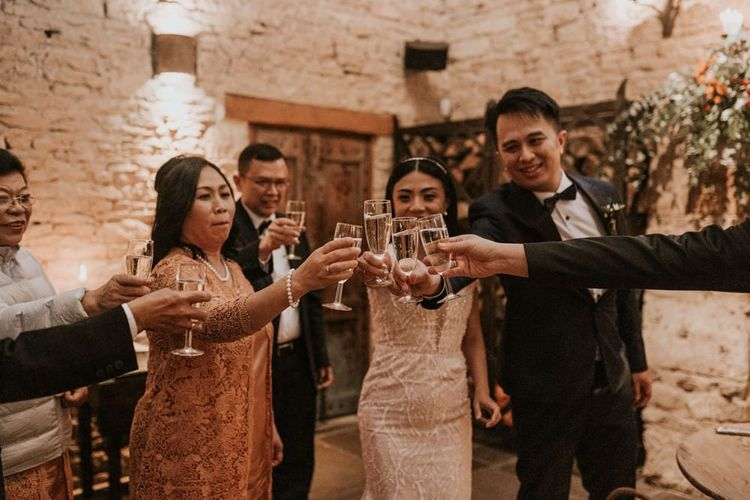 Bride and groom raising a toast with their family