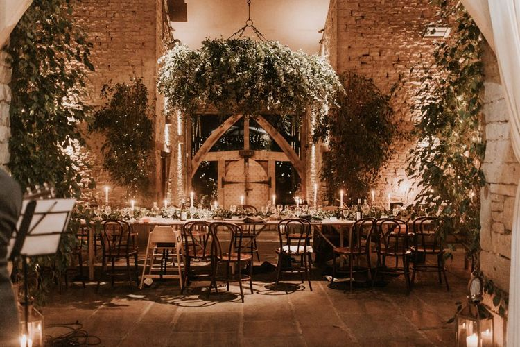 Foliage, candle and fairy lights wedding decor at rustic barn reception