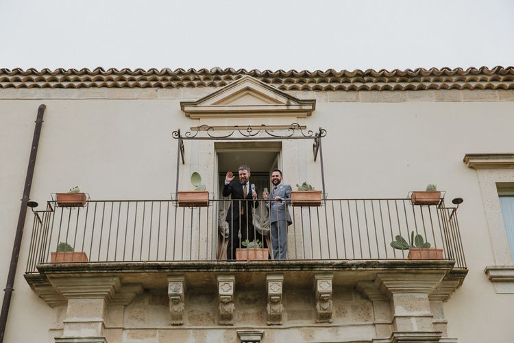 Grooms wave to guests on balcony of Sicilian wedding venue