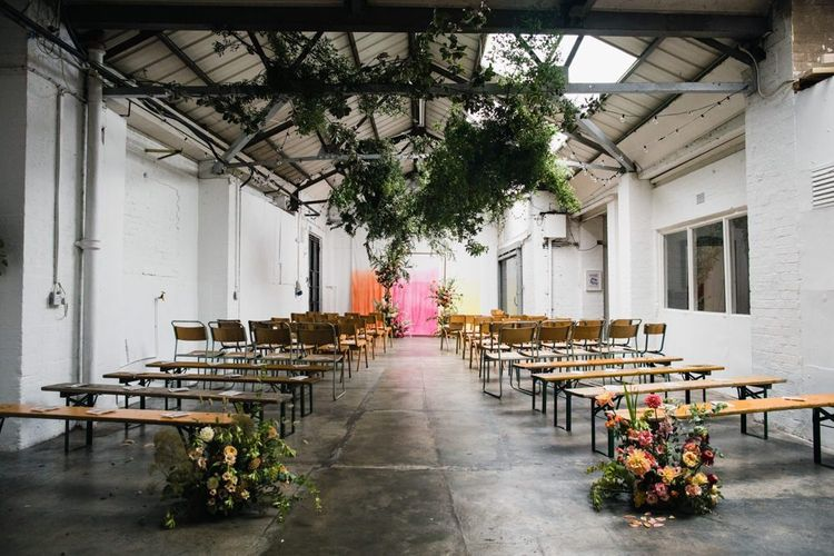Industrial wedding ceremony with hanging foliage and floral decor