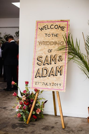Wooden wedding sign with floral decoration at industrial wedding ceremony