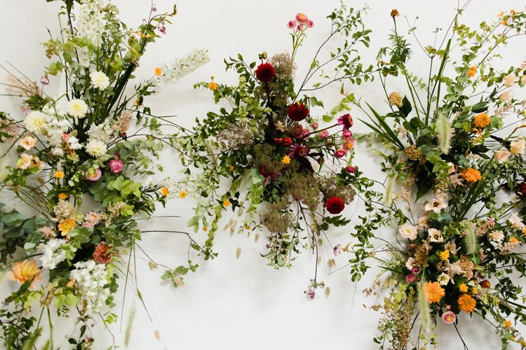 Orange and Pink floral decor with lots of foliage at industrial wedding ceremony