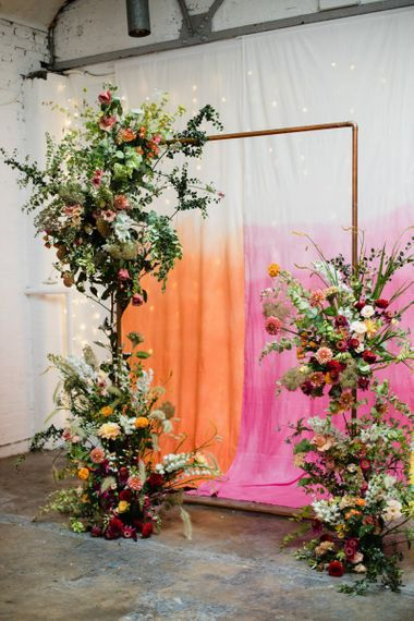 Hanging brightly coloured fabric backdrop with copper archway and floral decor