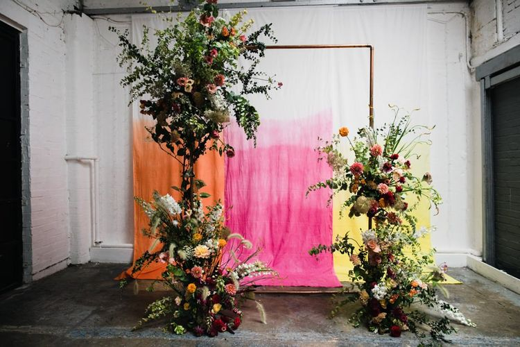Copper arch with bright floral decor at industrial wedding ceremony